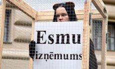 Foto: Cilvēks būrī pie Saeimas protestē pret dzīvnieku izmantošanu cirkā