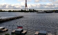 Foto: Spēcīgā vēja dēļ Rīgā applūst ielas un kafejnīca