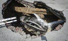 ASV milzīgs caurums uz ceļa 'aprij' automašīnu un vadītāju