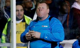 Sutton substitute Wayne Shaw eats a pie during the match