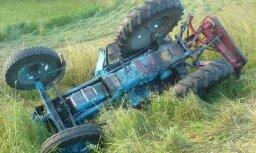 Traktorists pļāva zāli un apgāza traktoru