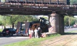 Zem dzelzceļa pārvada Sarkandaugavā izslīdējis traktors; kustība atjaunota