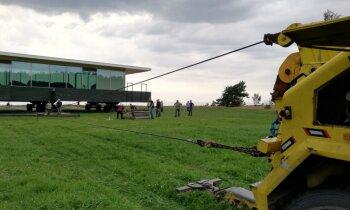 Foto: Evakuators aizvelk 'Māju-kuģi' pa pļavu; Lūsiņš 'piemirsis' informēt VVD