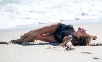Apetītlīga daiļaviņa vārtās pludmalē