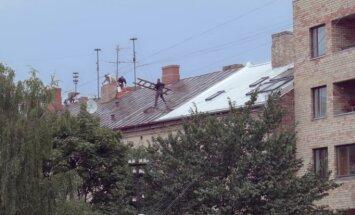 ВИДЕО: На мокрой крыше работает бригада строителей, подвергая опасности прохожих