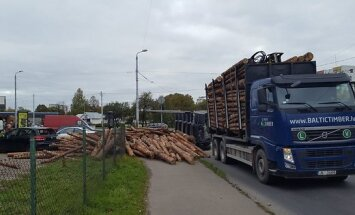 ФОТО: В Пурвциемсе перевернулся лесовоз; бревна упали на одну из машин