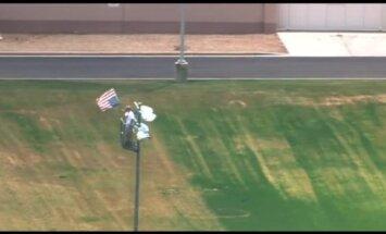 Video: Vīrietis uzrāpjas augstā gaismas stabā, vicina karogu un atsakās kāpt lejā