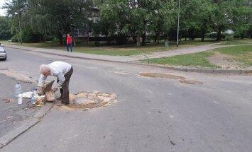 ФОТО: В Межциемсе пенсионер решил сам отремонтировать ямы на дороге