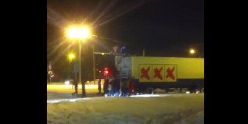 Jaunieši izstumj sniegā iestrēgušu kravas auto