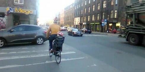 Tēvs ar velosipēdu ved savu bērnu pie sarkanās gaismas