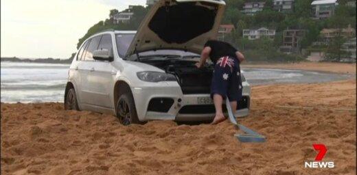 Video: Sidnejā pludmalē iestieg 'BMW X5', tikai traktors spēj palīdzēt