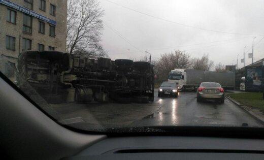 Foto: Pie 'Dominas' apgāzies smagais auto