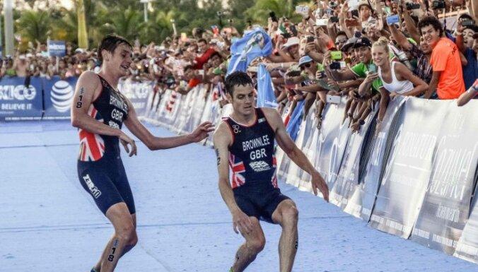 Alistair Brownlee helps brother Jonathan Brownlee, triathlon
