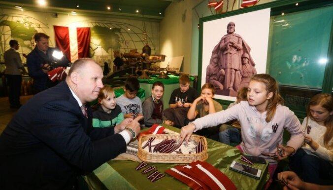 Foto: Aicinājumam Kara muzejā locīt sarkanbaltsarkanās lentītes atsaucas rekordliels skolēnu skaits