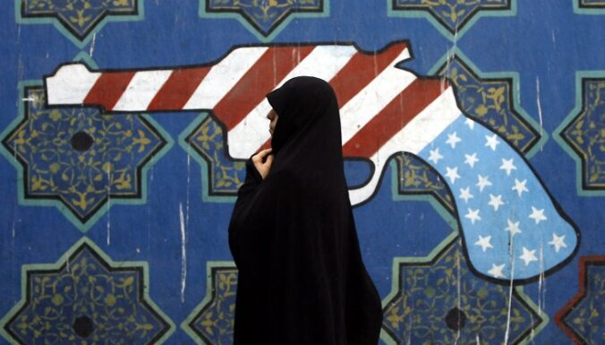 epa01920719 An Iranian woman walk past a mural outside former US embassy during during a demonstration marking the 30th anniversary of US Embassy takeover on 4 November 2009 in front of the former US embassy in Tehran , Iran.  EPA/ABEDIN TAHERKENAREH