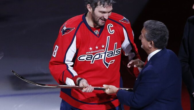 Washington Capitals owner Ted Elonsis gives a gold stick to Alex Ovechkin