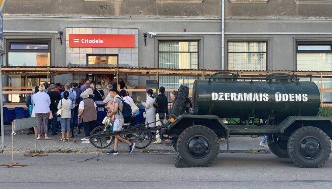 Foto: Daugavpilī pie bankām rindās stāvošajiem nodrošina soliņus un ūdensmašīnu