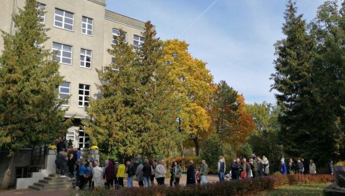 Foto: Saeimas vēlētājiem dažviet Rīgā pie iecirkņiem nākas gaidīt garās rindās