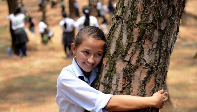 Foto: Nepālā divi tūkstoši cilvēku vienlaikus samīļo kokus