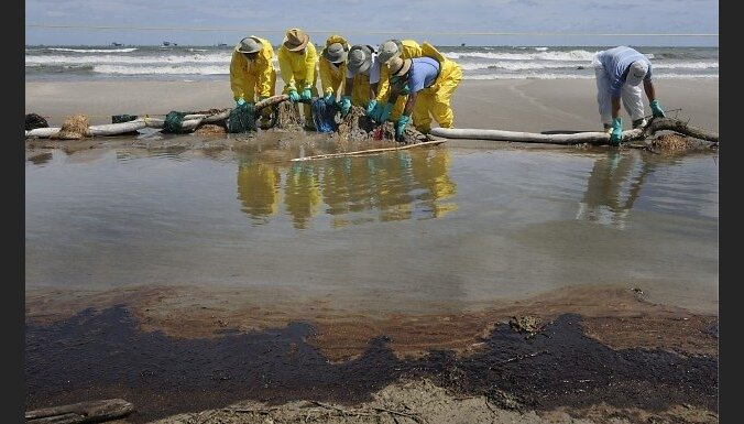 epa02228810 Clean-up workers pull up protective boom and absorbtion materal from the oil-stained beach in Port Fourchon, Louisiana, USA, 28 June, 2010 after oil from the BP Deepwater Horizon oil spill began to wash ashore early in the afternoon, leaving s