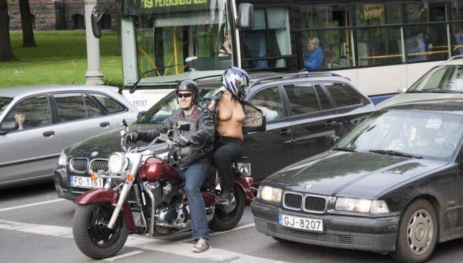 Daiļava uz motocikla atkailinās Rīgas autobraucēju priekšā
