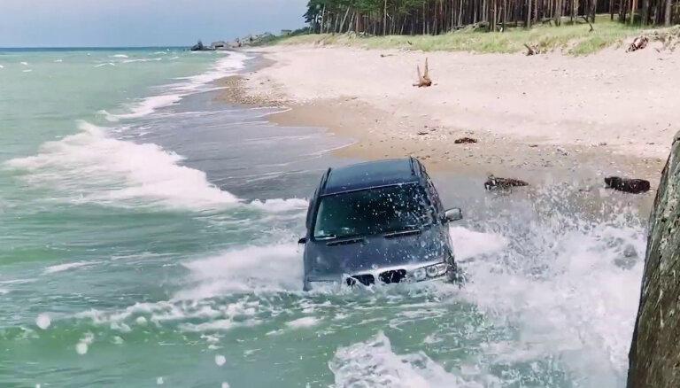 Video: Liepājas pludmalē jūras viļņi apskauj pamestu 'BMW X5' apvidnieku