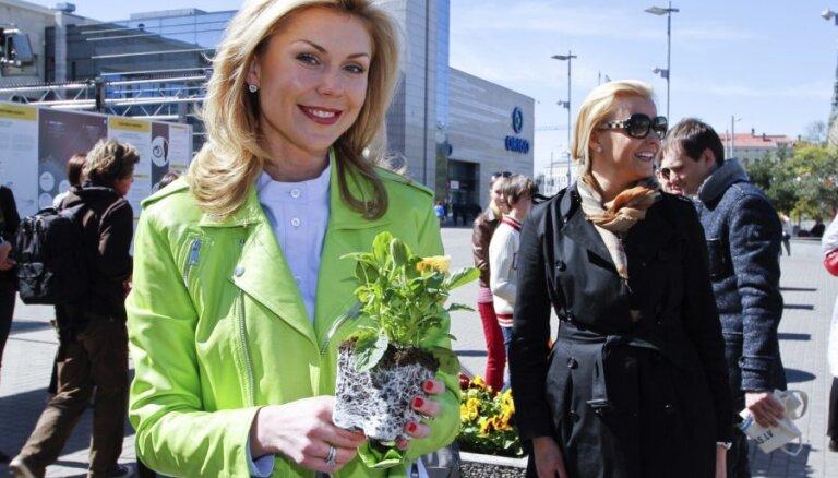 Foto: Zeltiņa un Rajecka pie 'Origo' stāda puķes