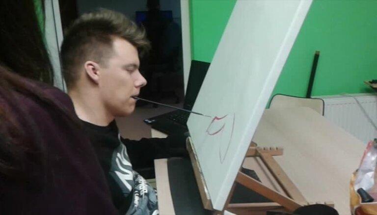 Paralizēts latviešu puisis glezno ar muti