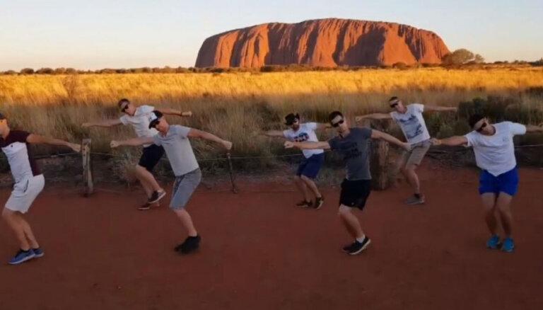 Sajūsmu gūst latviešu jaunekļu tautiskais dancis pie Uluru klints Austrālijā