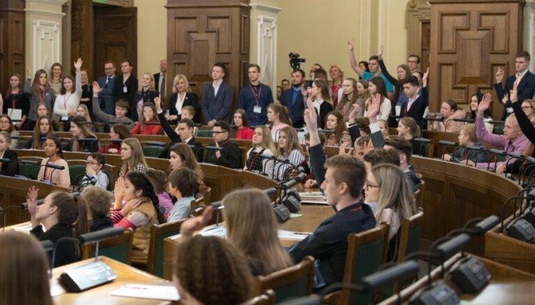 Foto: Saeimā teju 200 skolēni 'ēno' deputātus