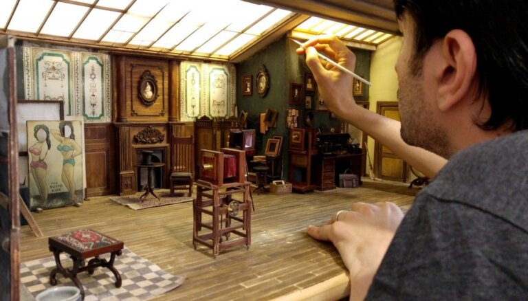 Vīrietis aiz bezdarbības rada miniatūru fotografēšanas studiju