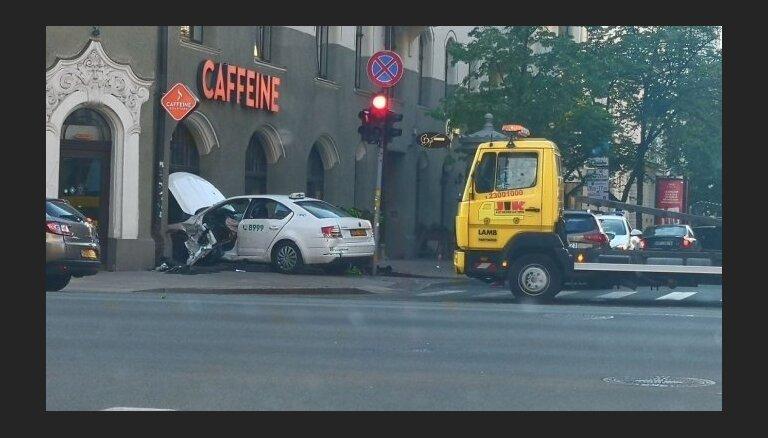 ФОТО: В Риге после столкновения такси врезалoсь в окно кафе, другая машина — в дверь аптеки