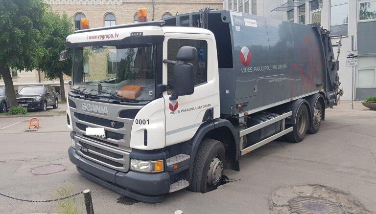 Foto: Atkritumu vedējs 'ielauž' ceļa segumu Rīgā