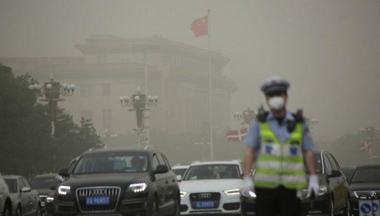 Foto: Smilšu vētra Ķīnu ietin putekļos