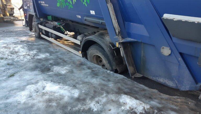 Foto: Atkritumu vedējs Rīgā iestieg lielā bedrē