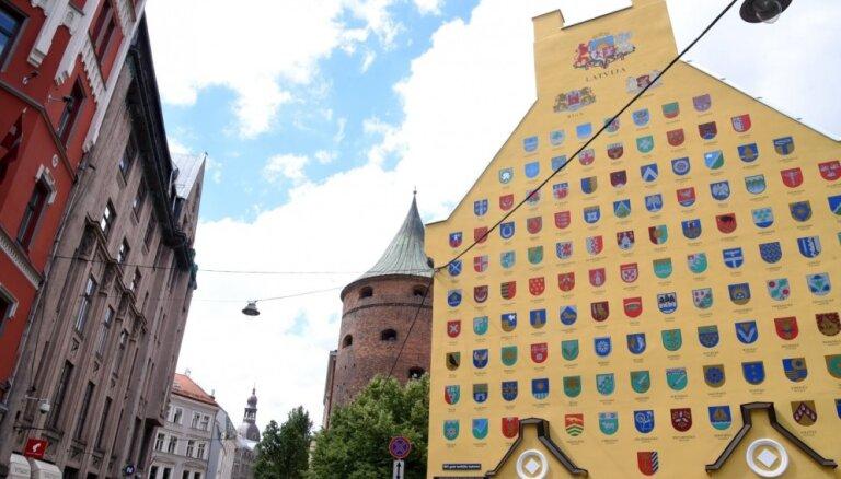 Foto: Rīgā atklāj atjaunoto Latvijas pašvaldību ģerboņu sienu